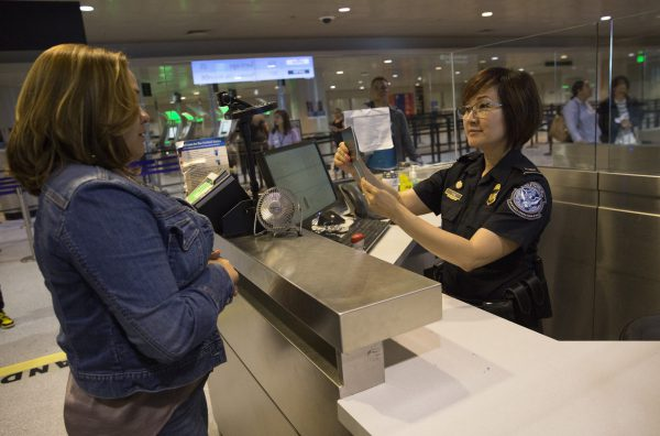 woman crossing us border interviewed by us customs and border protection agent